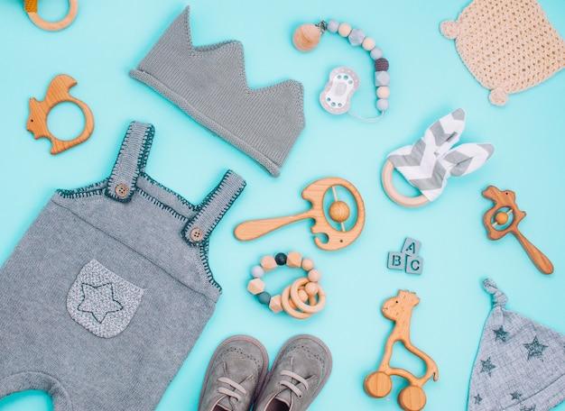 Vestiti per neonati e giocattoli in legno su azzurro