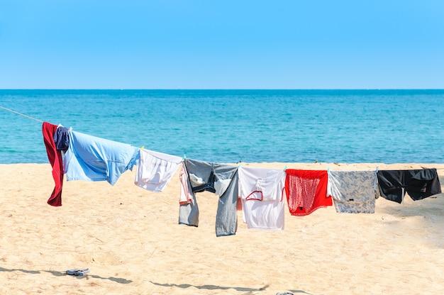 Vestiti variopinti che appendono per asciugarsi su una linea della lavanderia e sole che splende sulla spiaggia