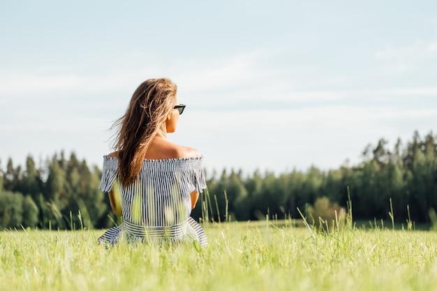 Vestito da portare dalla donna che si siede sul campo di erba verde