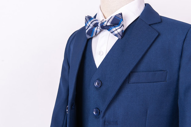 Vestito della giacca blu dei bei uomini con la camicia e farfallino su fondo bianco