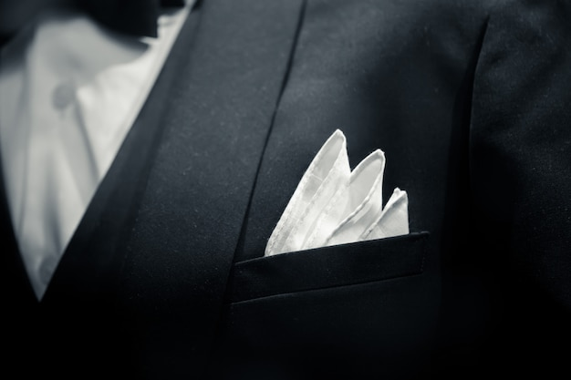 Vestito dello smoking dello sposo del primo piano dell'uomo delicato per il tono in bianco e nero di arte della cena di lusso.