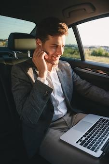 Vestito e auricolare d'uso del riuscito uomo che lavorano al computer portatile, mentre sedendosi indietro in automobile del business class