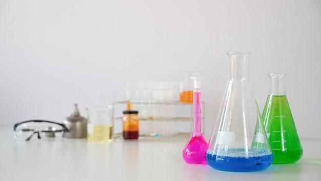Vetreria di laboratorio contenente liquidi colorati e occhiali di sicurezza mentre si uniscono sul tavolo.