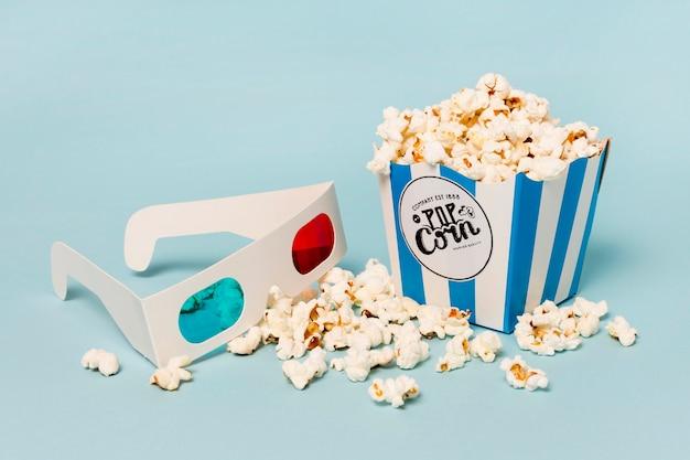 Vetri 3d con la scatola dei popcorn sul contesto blu