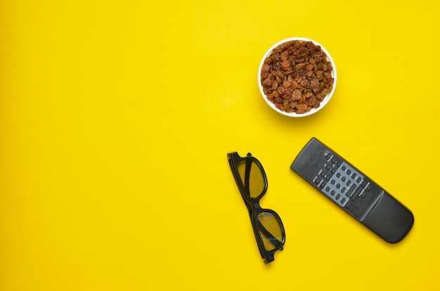 Vetri 3d, telecomando della tv, ciotola con l'uva passa su un fondo giallo, vista superiore
