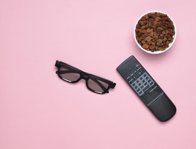 Vetri 3d, telecomando della tv, ciotola con l'uva passa su un fondo pastello rosa, vista superiore