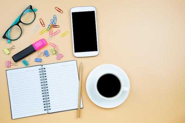 Vetri blu della tazza bianca del caffè nero del calcolatore del telefono cellulare del taccuino