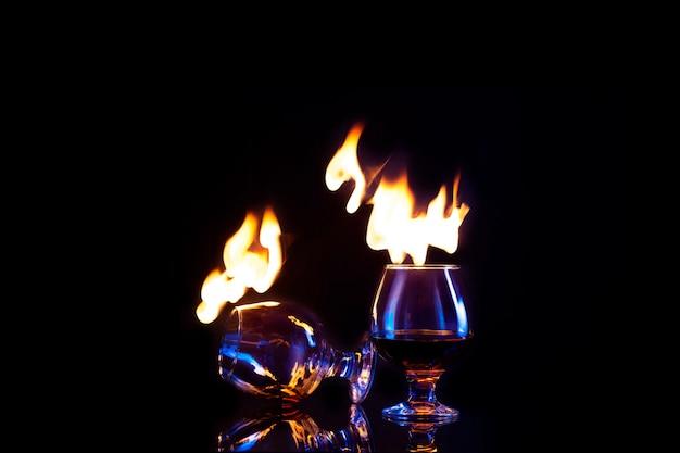 Vetri con alcool bruciante su oscurità