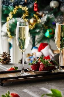 Vetri con champagne e le fragole con un albero di natale