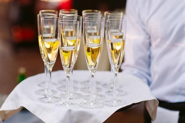 Vetri con champagne su un vassoio. incontro con gli ospiti.