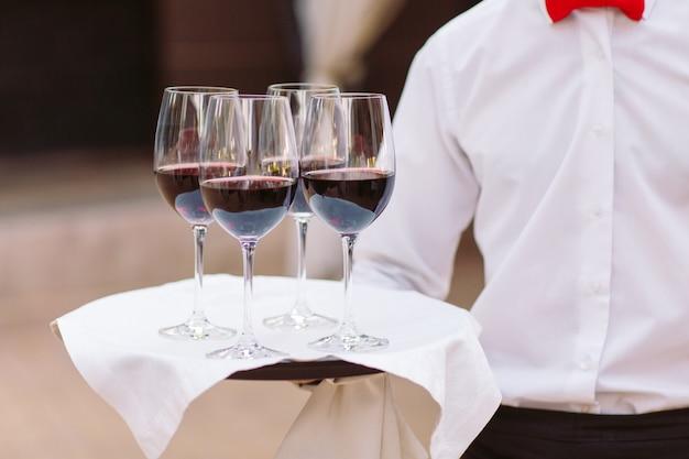 Vetri con vino su un vassoio. incontro con gli ospiti.