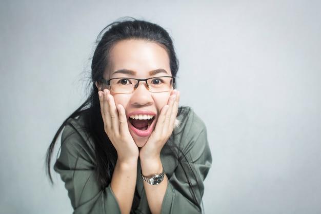 Vetri d'uso della donna asiatica sorpresa e felice su fondo grigio