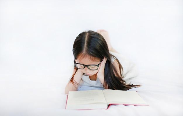Vetri d'uso della piccola ragazza asiatica del bambino che leggono libro dalla copertina rigida che si trova sul letto contro il fondo bianco.