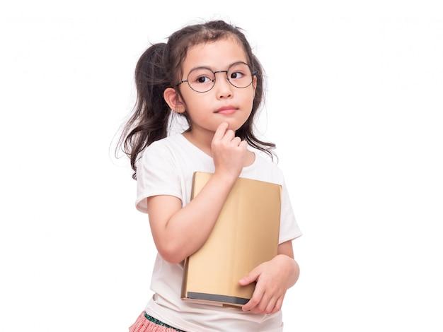 Vetri da portare della piccola ragazza sveglia asiatica e tenere un libro sulle mani.
