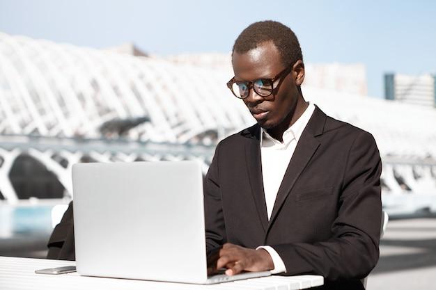 Vetri da portare seri del giovane imprenditore dalla pelle scura facendo uso del computer portatile generico per lavoro a distanza mentre aspettando i soci commerciali al caffè all'aperto.