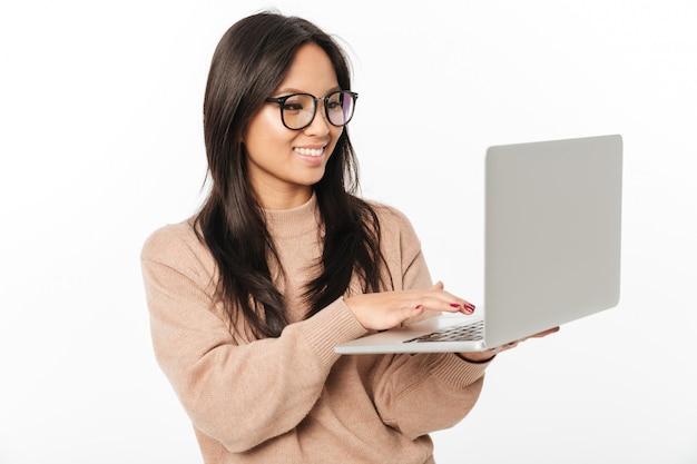 Vetri da portare sorridenti asiatici della donna per mezzo del computer portatile