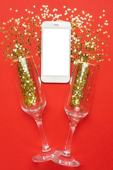 Vetri del champagne e del telefono cellulare con il concetto dorato dei coriandoli, di natale e del nuovo anno delle stelle