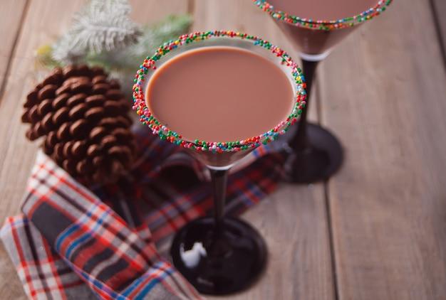 Vetri del cocktail di cioccolato di stagione invernale, ramo dell'albero di natale con la pigna di legno