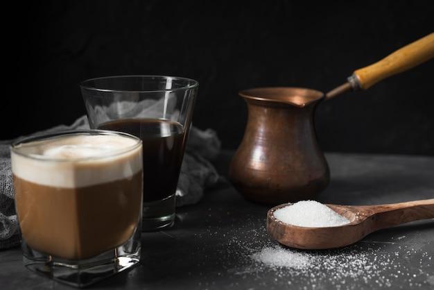 Vetri del primo piano con caffè e zucchero