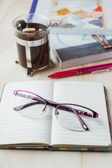 Vetri della donna con il taccuino, il caffè, la matita e il libro