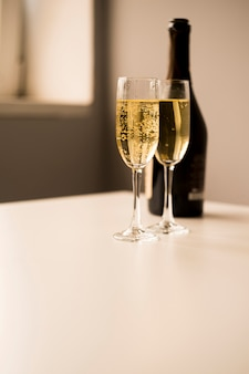 Vetri di champagne con la bottiglia sulla tavola bianca