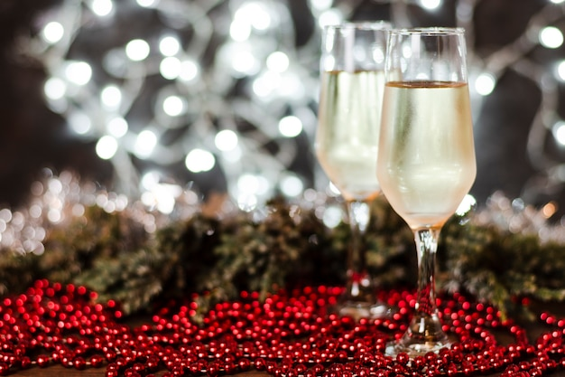 Vetri di champagne con le luci di natale nei precedenti