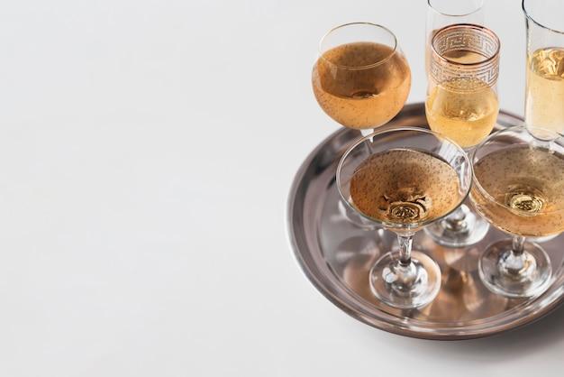 Vetri di champagne su un vassoio con lo spazio della copia