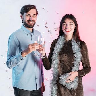 Vetri di champagne tintinnanti delle coppie che celebrano il natale