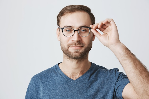 Vetri di raccolto attraenti dell'uomo barbuto al deposito dell'ottico