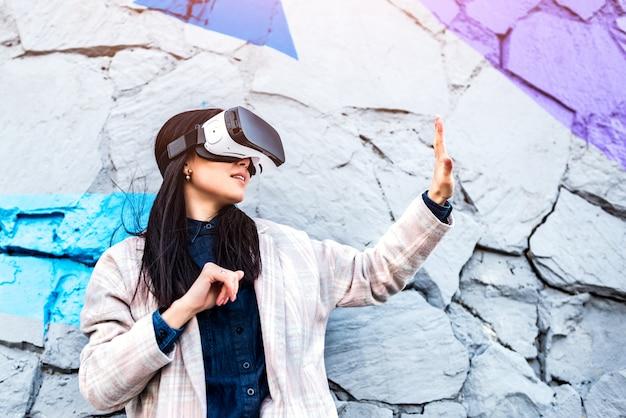 Vetri di realtà virtuale godenti all'aperto della ragazza graziosa