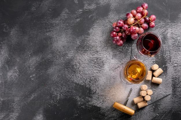 Vetri di vino di vista superiore con gli spazi della copia e dell'uva a sinistra sull'orizzontale di pietra nero