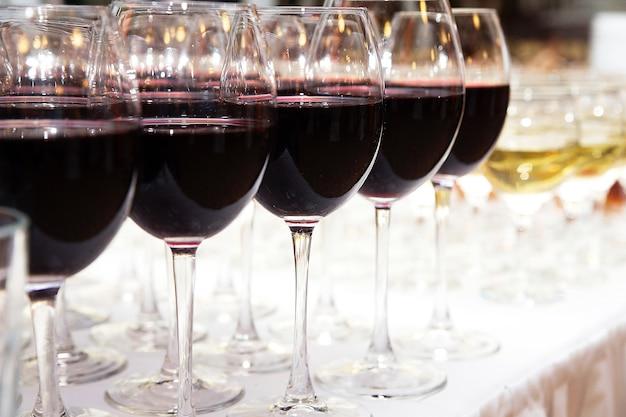 Vetri di vino rosso sul primo piano bianco della tavola