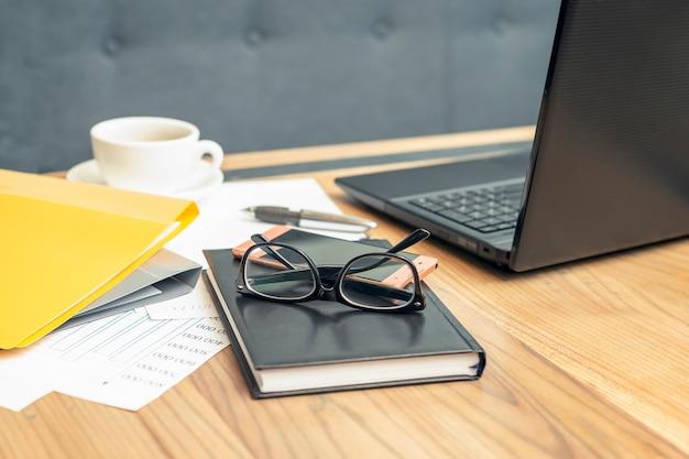 Vetri di vista laterale, smartphone, computer portatile, taccuino e penna sulla tavola di legno.