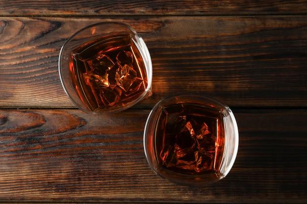 Vetri di whiskey con i cubetti di ghiaccio su fondo di legno, vista superiore