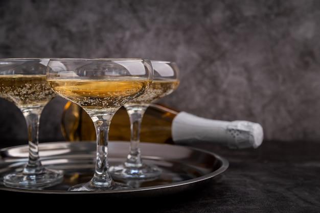 Vetri e bottiglia con champagne su un vassoio su oscurità