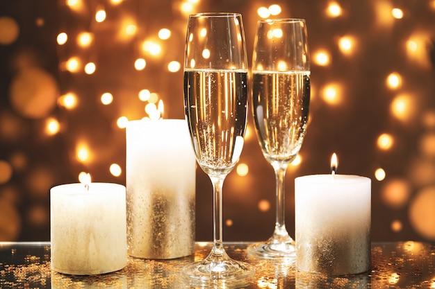 Vetri e candele di champagne contro lo spazio delle luci vago, spazio per testo