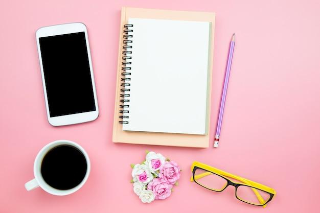 Vetri gialli della rosa del fiore del caffè nero del telefono cellulare del taccuino su fondo rosa