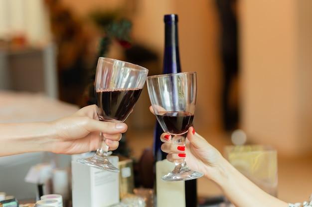 Vetri tintinnanti a mano con vino bianco per la festa di celebrazione.