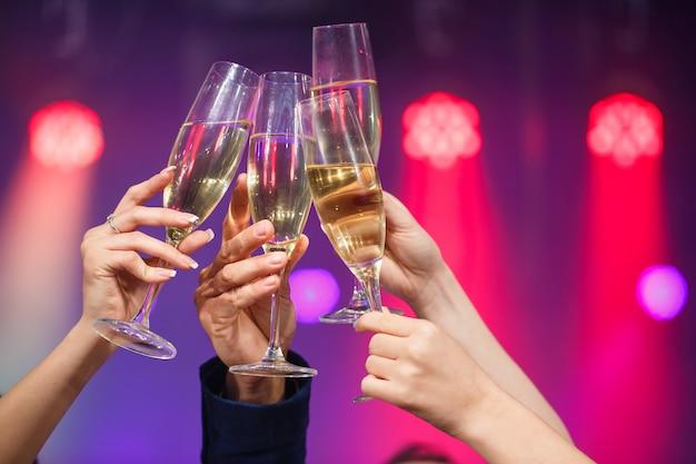 Vetri tintinnanti di champagne in mani sul fondo delle luci intense