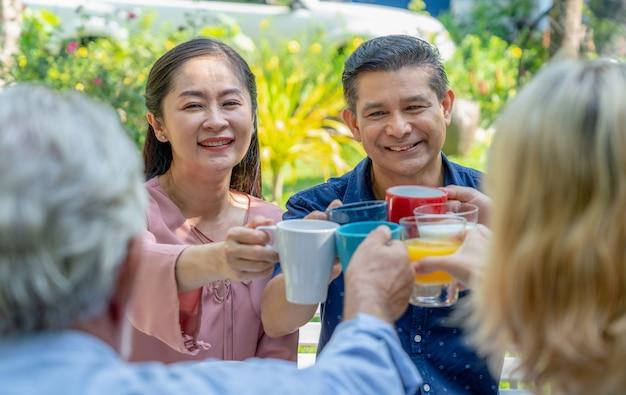 Vetri tintinnanti senior delle coppie felici con la loro famiglia mentre giardino della prima colazione insieme a casa