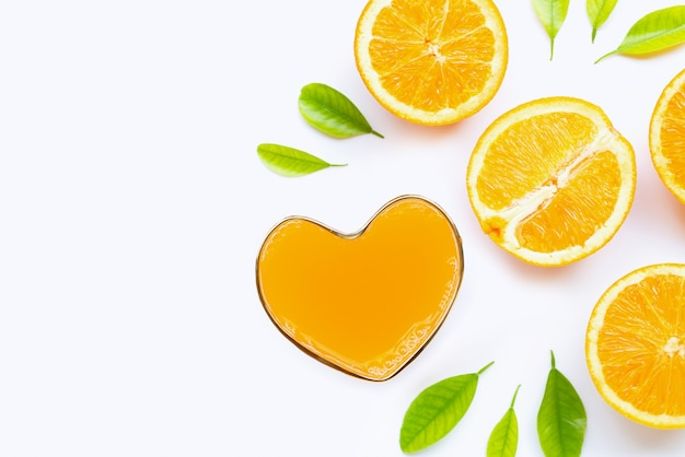 Vetro a forma di cuore di succo d'arancia fresco con frutta arancione su bianco. vista dall'alto con spazio di copia