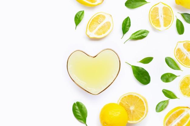 Vetro a forma di cuore di succo di limone appena spremuto con limone fresco su sfondo bianco