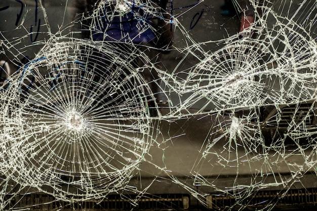 Vetro auto incrinato per caso, sfondo di trame di vetro rotto