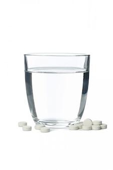 Vetro con acqua e pillole isolate su bianco