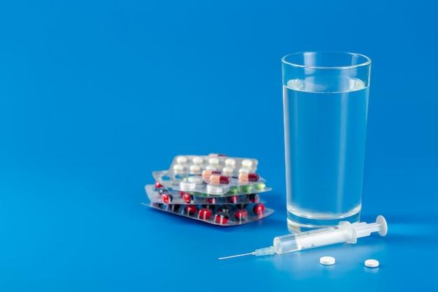Vetro con acqua, pillole, siringa su sfondo blu con spazio di copia