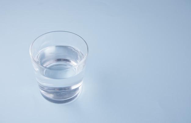 Vetro con acqua su sfondo blu