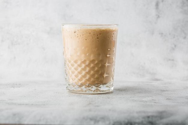 Vetro con caffè freddo e latte isolati su fondo di marmo luminoso. vista dall'alto, copia spazio. pubblicità per menu bar. menu della caffetteria. foto orizzontale.