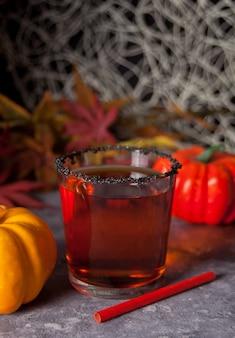 Vetro con cocktail di zucca con foglie di autunno e zucche sullo sfondo