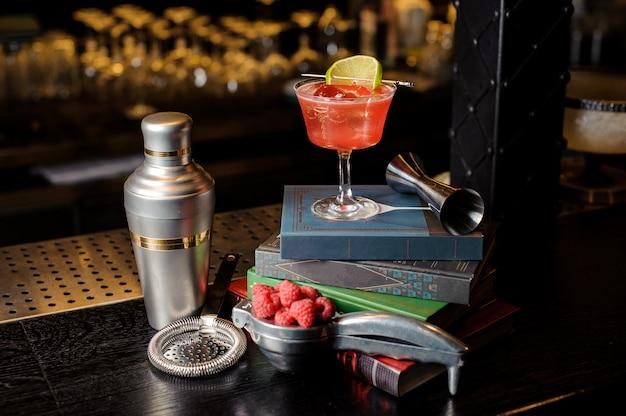 Vetro con cocktail estivo dolce fresco con fetta di lime su libri
