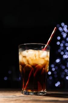 Vetro con cola, fetta di lime e tubulo su sfondo di luci sfocate